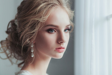 Morning of the bride. Beautiful young woman in elegant white robe with fashion wedding hairstyle standing near the window