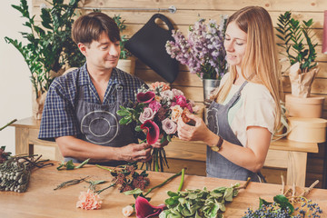 Florist and assistant in flower shop delivery make rose bouquet