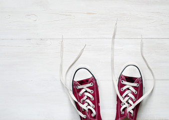 Claret sneakers on wooden white floor background, top view. Conceptual image of a dancing couple, youth, dance floor