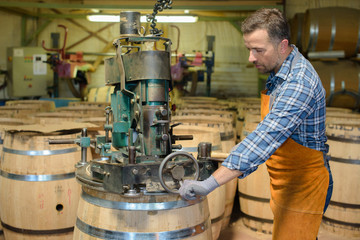 Cooper using machine to make barrel