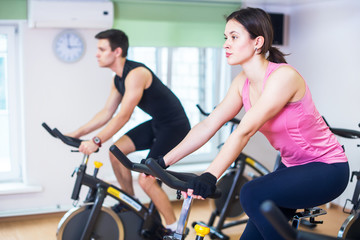 Group training people biking in the gym, exercising legs doing cardio workout cycling bikes