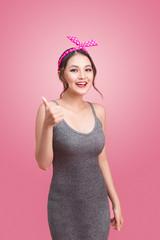 Beautiful asian girl with pretty smile in pinup style on pink ba