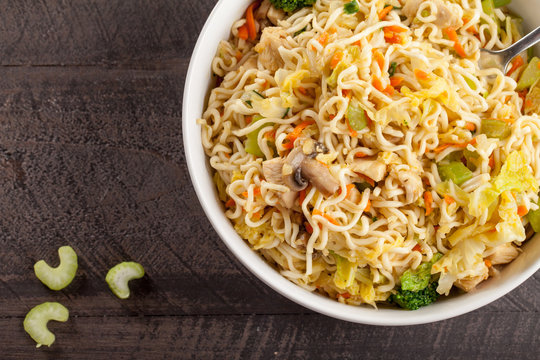 Chinese chicken lo mein with cabbage, carrots, celery, mushrooms, turnips, broccoli, and assorted vegetables top view
