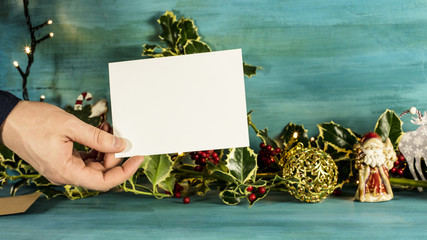 Hand holding blank card in front of Christmas background