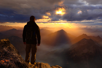 Man standing on the top of a mountain watching sunset sunrise