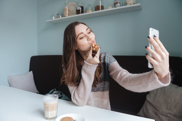 Cute lady sitting in cafe and making selfie with cookie
