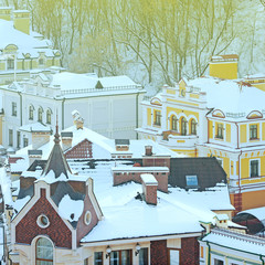 roofs of houses painted in different colors covered with snow and the sun