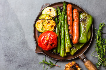 Grilled vegetables zucchini, asparagus, bell pepper, sausages on grill pan