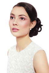 Young beautiful bride with stylish make-up and prom hairdo over white background