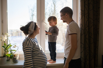happy family with  son kid toddler playing near window