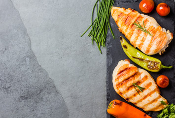 Grilled chicken fillets, chili and tomatoes on black slate plate