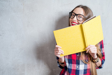 Portrait of a young happy student in checkered shirt with yellow book on the gray wall background