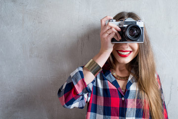Portrait of young female photographer with retro camera on the gray wall background