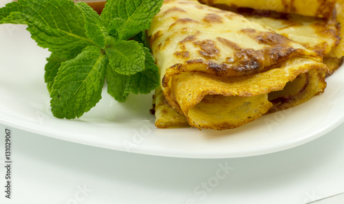 "Crepes on a white plate with mint leaves and a Cup of honey"" Stock ..."