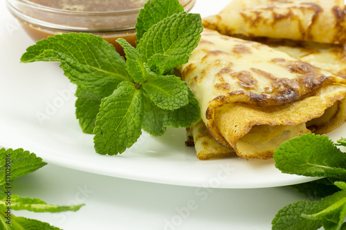 Foto: Crepes on a white plate with mint leaves and a Cup of honey
