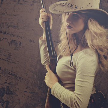 Wild west. Female portrait of cowgirl with vintage hunting rifle