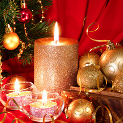Burning candle, Christmas balls and fir tree. Red background