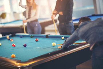 Group of young friends playing billiard