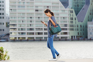 young woman walking by the water using cell phone