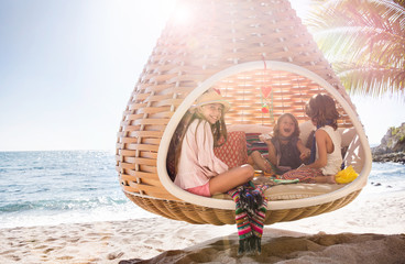 Young kids sitting togething in a hanging basket on the beach of a resort playing cards and relaxing in Mexico.