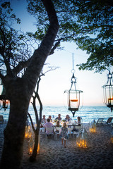 A group of friends and family eat dinner at a private table on a beach, surrounded by candle lanterns. Mexico.