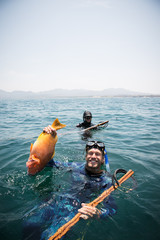 Man in a wet suit posing for photo with his fish caught while spearfishing