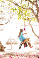 Young girl swinging on a tree swing at a beach resort.