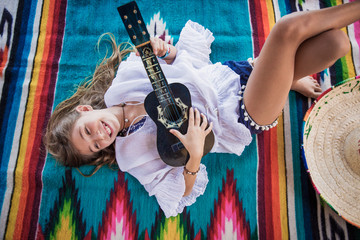 young girl plays ukulele while laying on a colorful Mexican blanket