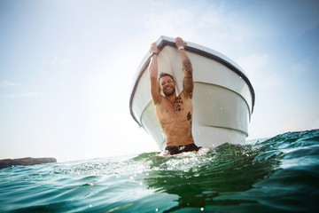 Attractive man hanging off a boat in the ocean