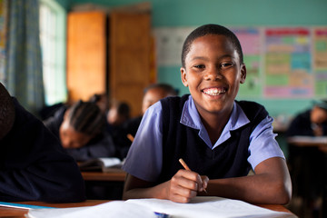 Young boy, looking at camera, doing class work at a desk in a classroom in Sounth Africa