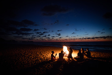 Friends sit around a bonfire on the beach, laughing dancing and drinking in the evening hours.