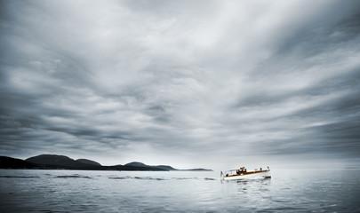 Boat on a blue foggy ocean. Maine