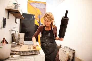 Female artist at work in her studio cleaning up her inks