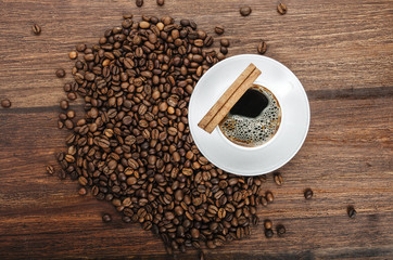 Coffee cup with cinnamon sticks and coffee beans on wooden table