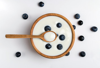 Fotobehang Zuivelproducten White yogurt in natural wooden bowl with blueberries. Top view on white background.