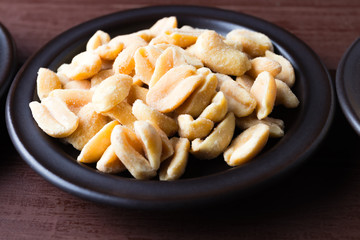 Hazelnuts and peanuts on a dark plate.