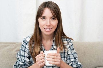 woman sitting on couch in her living room and drinking coffee