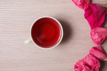 Red flowers and red tea in a white mug lying on the wooden backg