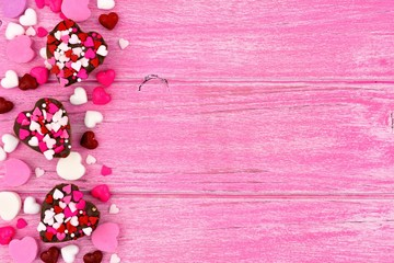 Valentines Day heart shaped candy side border against a rustic pink wood background