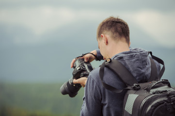 man photographer takes pictures in mountain