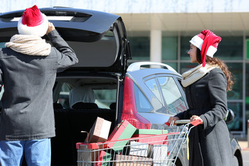 Printed kitchen splashbacks Athens Young couple loading Christmas purchases into car trunk on shopping mall parking