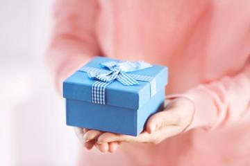 Female hands holding gift box, closeup