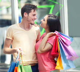 Happy couple with colorful shopping bags near shopping center