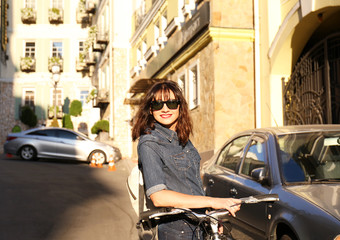 Pretty young woman with bicycle outdoors