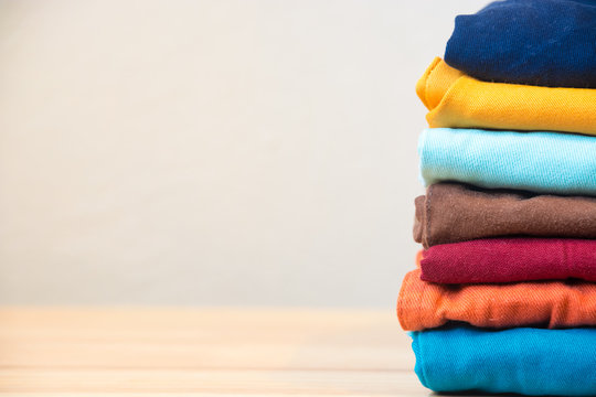 Stack of colorful clothes on wood table, Housework and objects concept