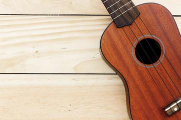 close-up ukulele on wood background. over light
