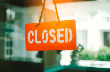 Closed sign hang on mirror door front of office room.
