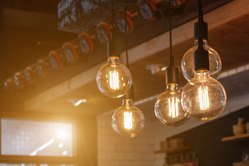 Decorative antique style filament LED light bulbs in restaurant with sunlight background.