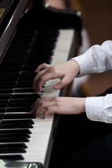 Hands of a child playing the piano closeup in dark colors