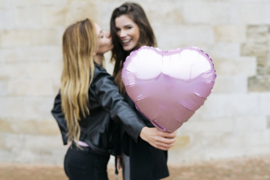 Smiling young couple holding heart balloon while kissing outdoors